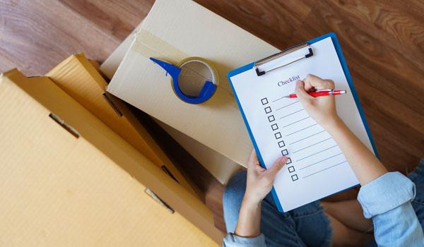 Femme préparant son déménagement avec un checklist