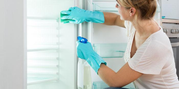 Dame en train de nettoyer un réfrigérateur