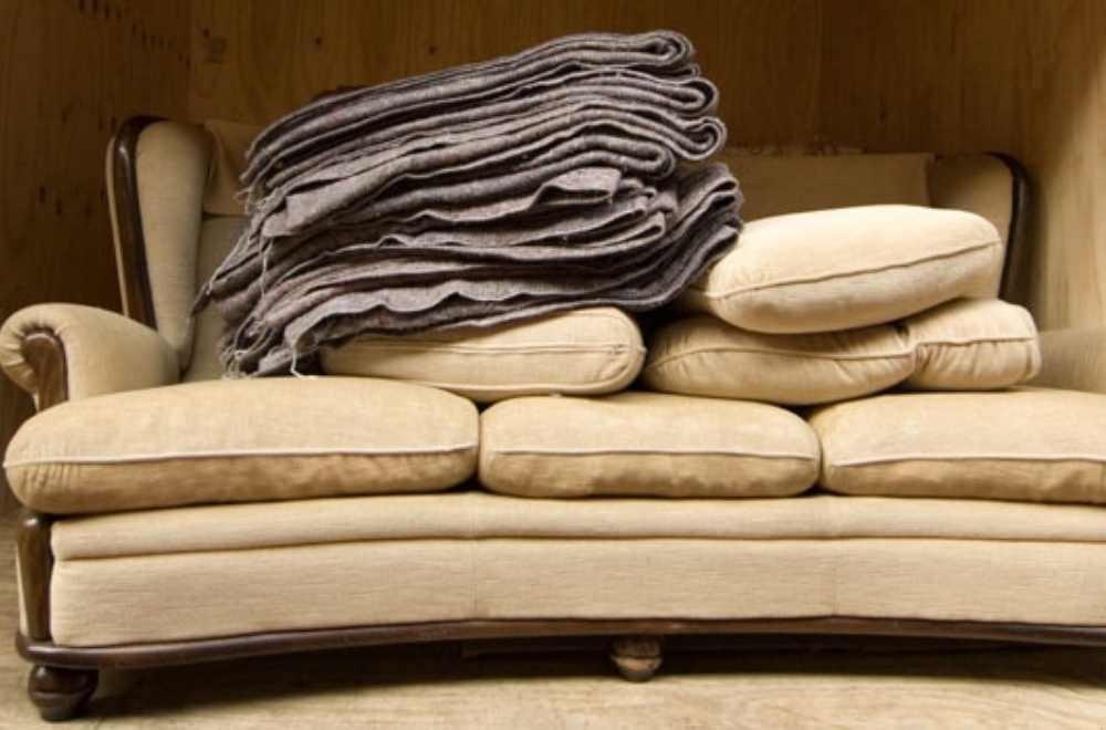 garde meuble avec un canapé et des couvertures de protection