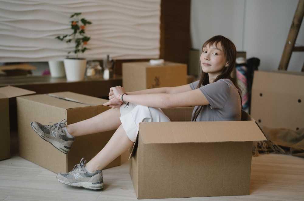 femme au milieu des cartons pendant son déménagement